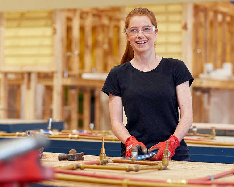 Woman wearing goggles standing in a construction workshop. She is smiling.